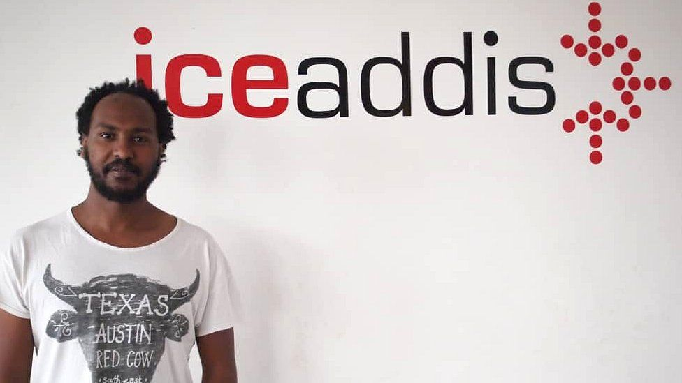 Markos Lemma in front of a logo for his co-working space IceAddis