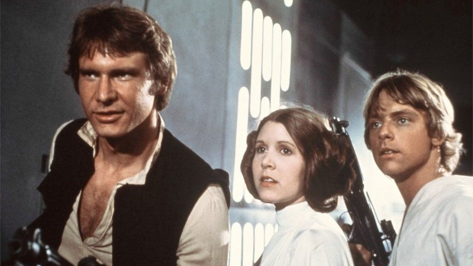 Harrison Ford, Carrie Fisher, and Mark Hamill are shown in a scene from Star Wars