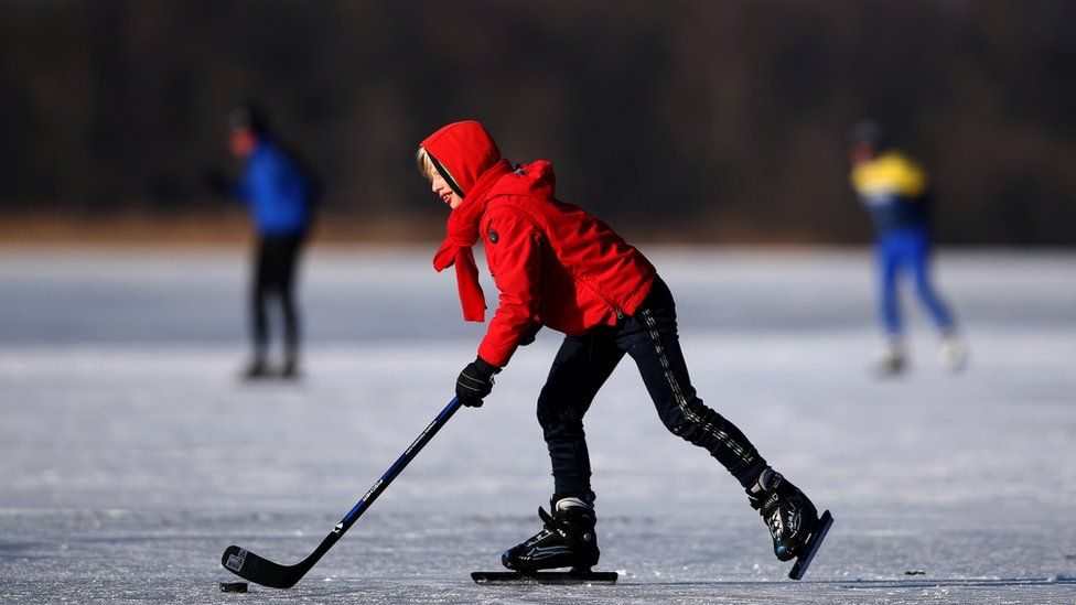 A boy plays ice hockey on the Nannewiid, a lake frozen over as temperatures stay below zero and locals enjoy activities like speed skating, ice hockey, using sleds and walking dogs on February 12, 2021 in Oudehaske, Netherlands.