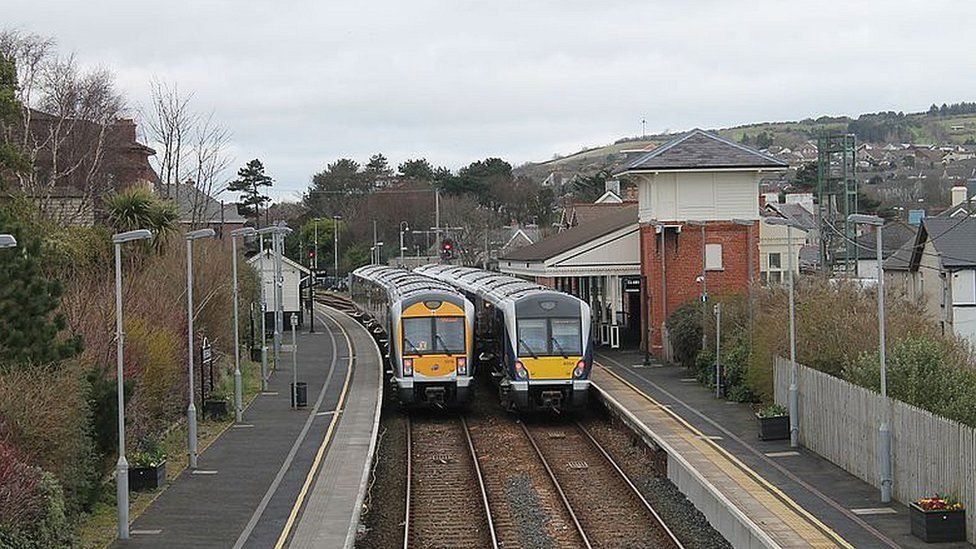 Two trains pass each other at Whitehead station