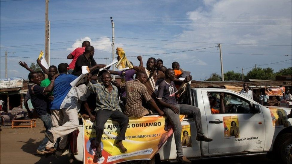 Men ride on top of a vehicle during a primaries el