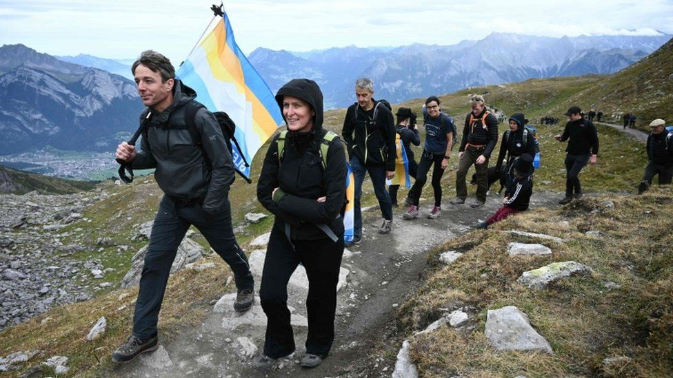People take part in a funeral march for a glacier lost to global warming