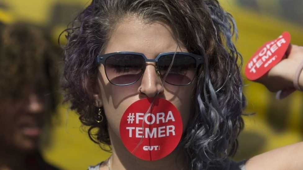 "A supporter of Dilma Rousseff, her mouth covered with a sticker that reads in Portuguese; ""Temer out"", takes part in a protest in front of the National Congress, where the impeachment trial of Rousseff is taking place, in Brasilia, Brazil, Tuesday, Aug. 30, 2016."