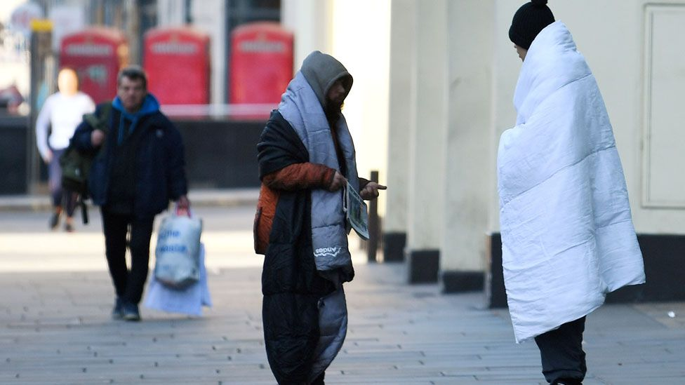 Homeless people stand on a pavement during rush hour in Central London, as the spread of the coronavirus disease (COVID-19) continues, in London, Britain