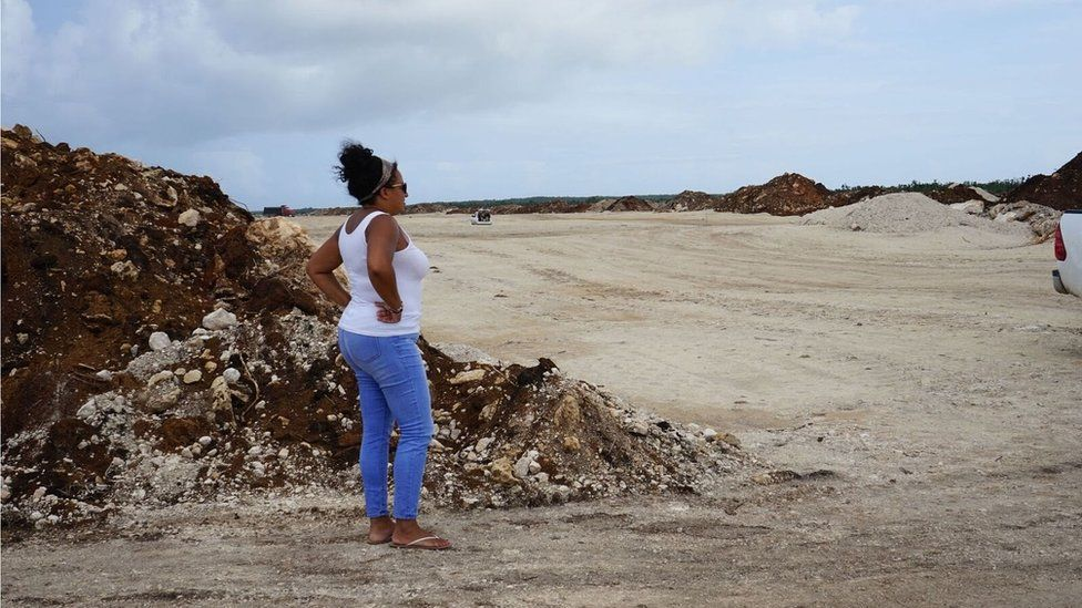 A woman looks on as construction work is under way for a new runway