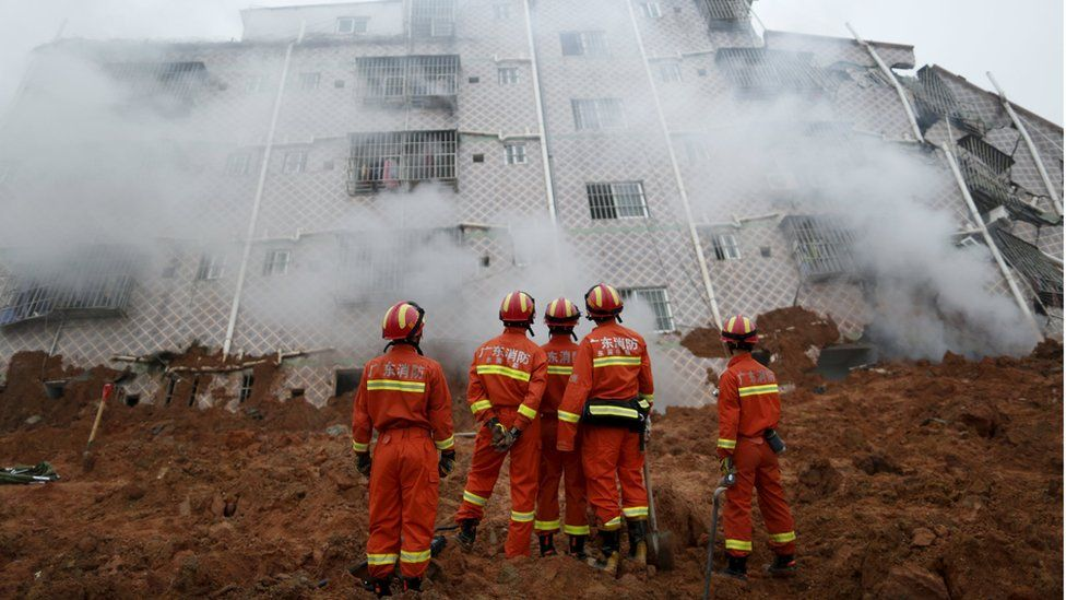 Firefighters look on as smoke rises in front of a damaged building at the site of a landslide at an industrial park in Shenzhen, Guangzhou, China, December 20, 2015.