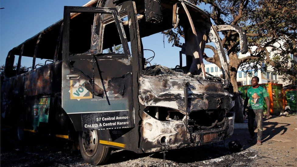 "A supporter of the ruling ZANU-PF walks past a burnt vehicle at the party""s offices a day after the clashes between security forces and opposition protesters in Harare, Zimbabwe, August 2, 2018"