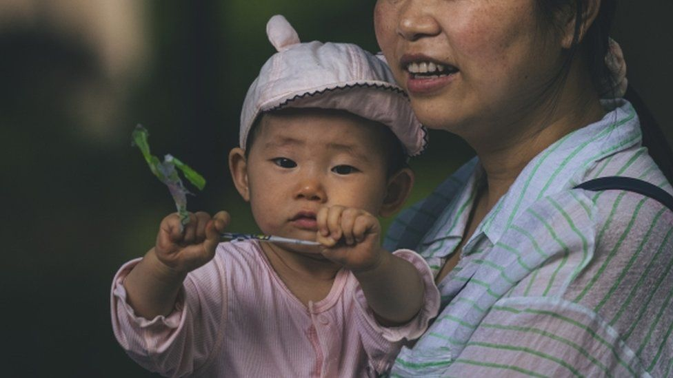 A woman walks with a baby on a street in Shanghai, China, 31 May 2021.