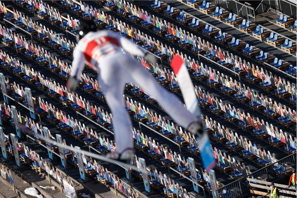 A ski jumper flies through the air with hundreds of cardboard cut outs of people below
