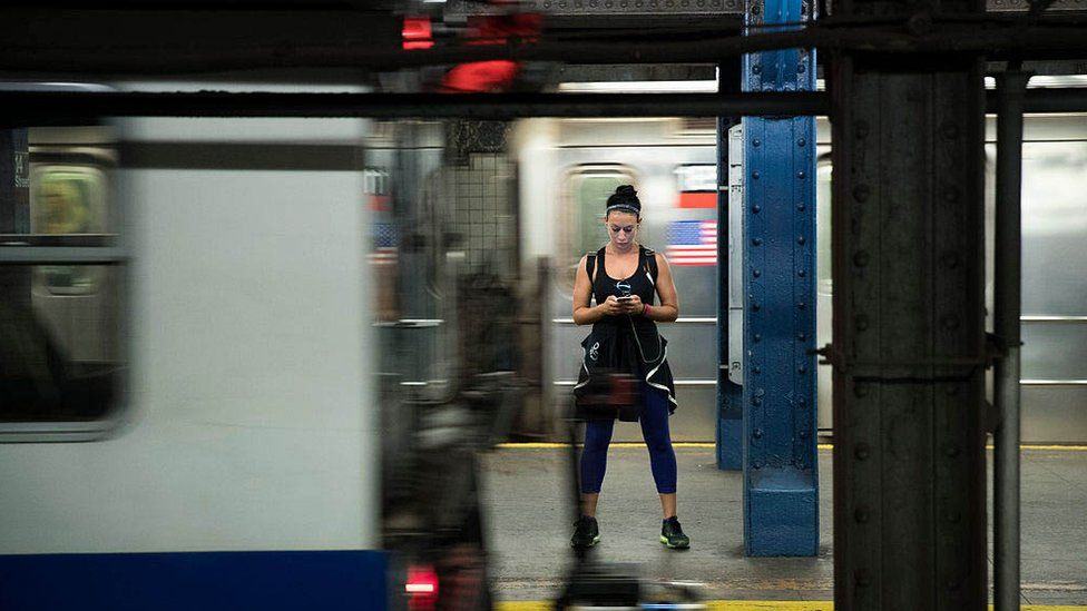 Woman looks at her phone on the New York subway