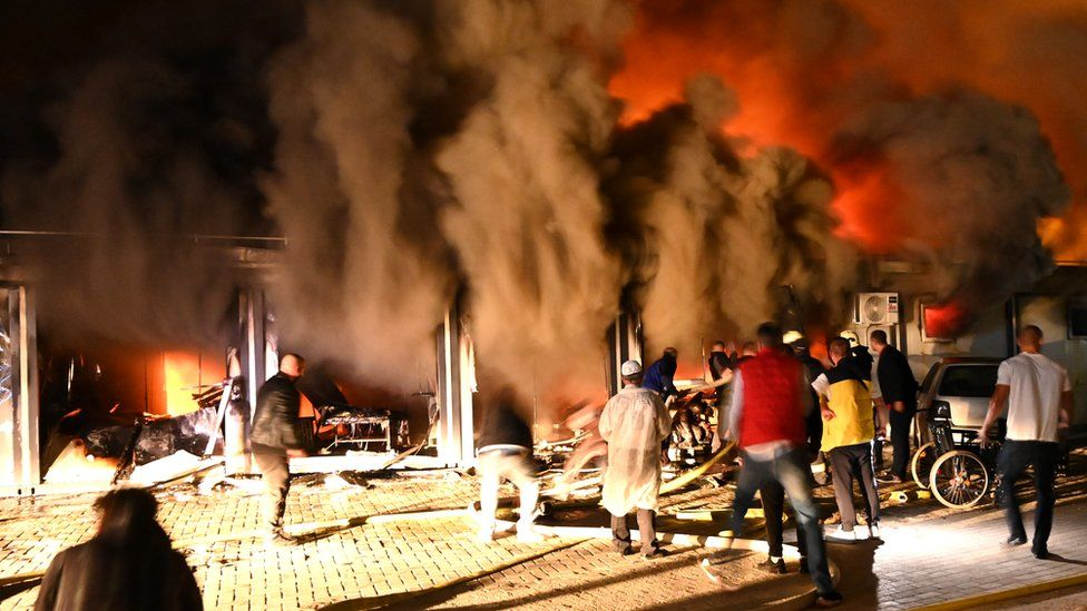 Smoke rises as firefighters and civilians try to extinguish a blaze that broke out at a hospital for Covid-19 patients in Tetovo, Republic of North Macedonia, 8 September 2021