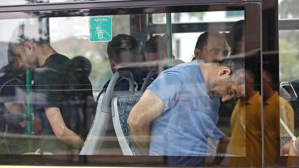 Turkish plain cloth policemen accompany detainee soldiers after the 15 July failed coup attempt at a bus as they arrive to Istanbul court