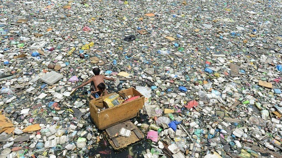 A father and son on a makeshift boat paddle through a garbage-filled river in Manila in 2015