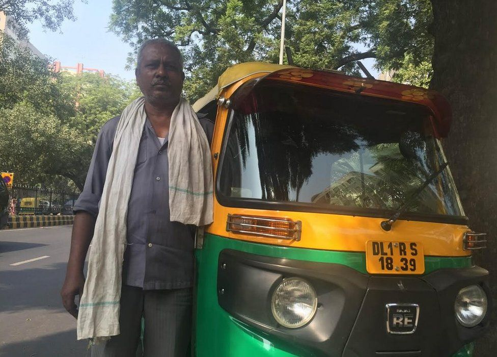 Mahendra Sharma standing next to his tuk tuk