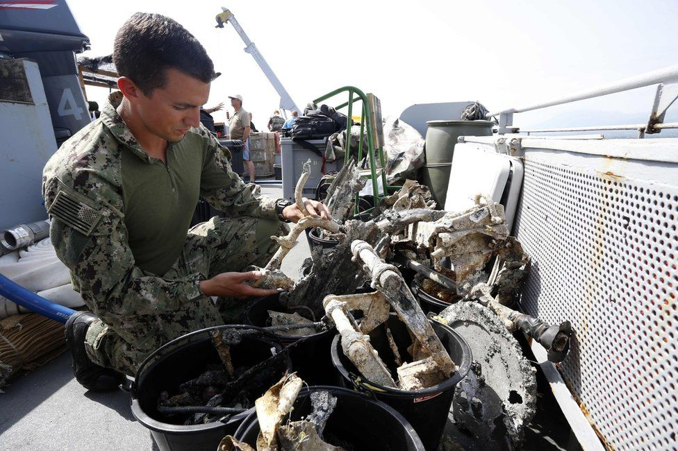 An American officer inspects fragments of a plane on the deck of the French FS Pluton M622 navy de-mining ship