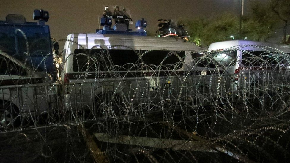 Thai police at a barricade of barbed wire and buses to halt protesters in Bangkok