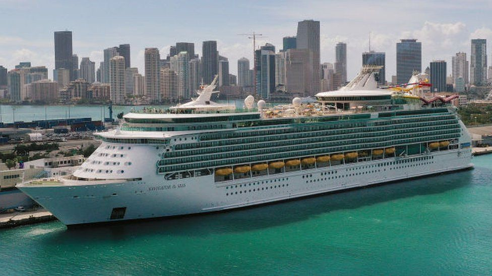 cruise ship docked in Miami with city skyline behind it