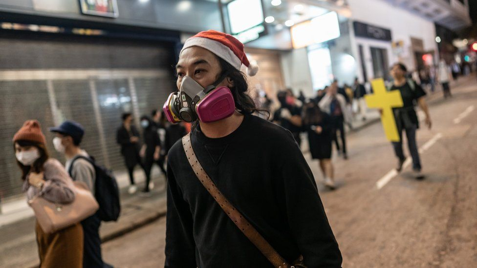 A protester reacts after police fire tear gas to disperse bystanders in a protest in Jordan district in Hong Kong, on early December 25, 2019.