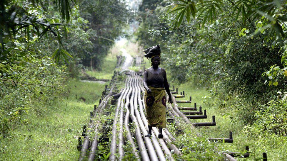 A woman walks along an oil pipeline near Shell's Utorogu flow station in Warri, Nigeria, Sunday, Jan. 15, 2006.