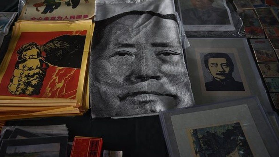 A cloth print featuring a portrait of late communist leader Mao Zedong (C) lies on the ground at a market in Beijing on October 25, 2015