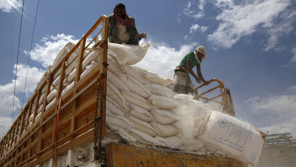 A worker stands on a vehicle carrying food and medical supplies provided by the World Food Program in Sanaa, Yemen