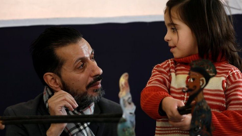 Shadi al-Hallaq, a puppeteer, is seen next to a disabled child during a performance in Damascus, Syria on 3 December 2018.