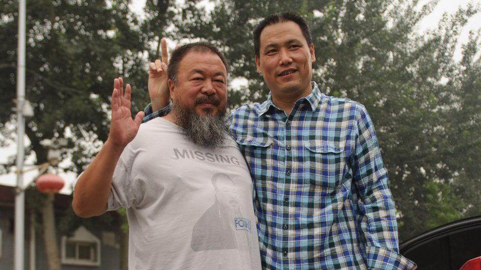 File photo: Pu Zhiqiang (R) stands with dissident artist Ai Weiwei (L) in the Caochangdi district of Beijing, 20 July 2012