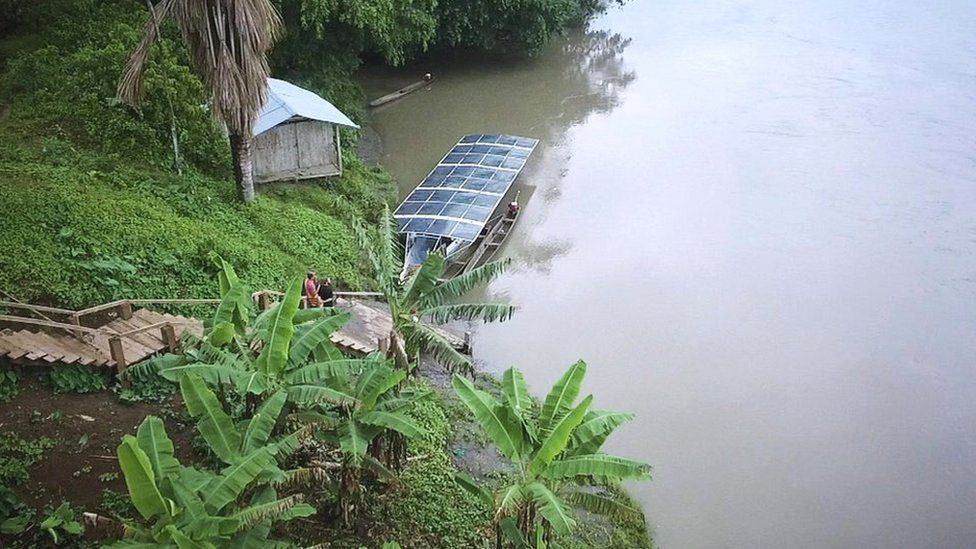 The solar canoe tied up at a village port