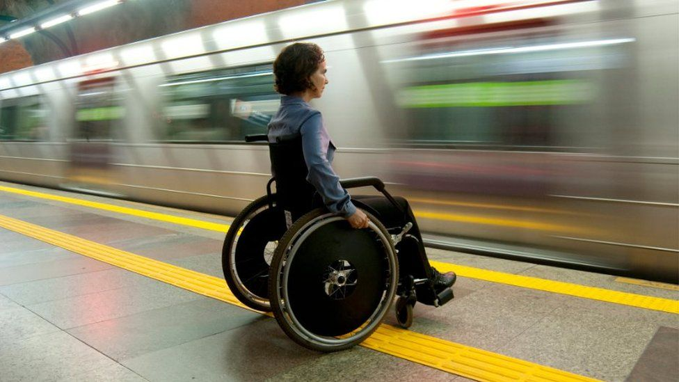 Wheelchair user on a platform with a train going past