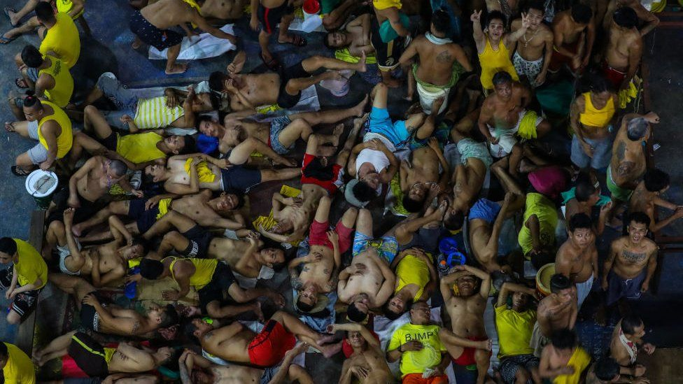 This photo taken on March 27, 2020 shows prison inmates sleeping and gesturing in cramped conditions in the crowded courtyard of the Quezon City jail