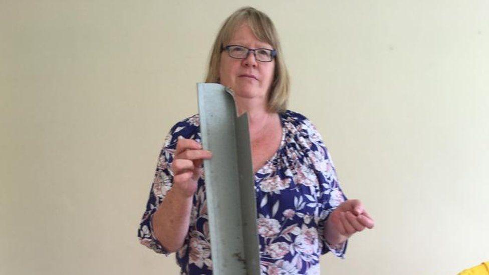 Pauline Sadler holds a piece of cladding