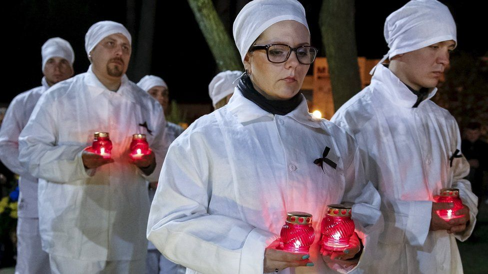 Staff of the Chernobyl nuclear plant hold candles as they visit a memorial, dedicated to firefighters and workers who died after the Chernobyl nuclear disaster, during a night service in the city of Slavutych, Ukraine, April 26, 2016. REUTERS/Gleb Garanich