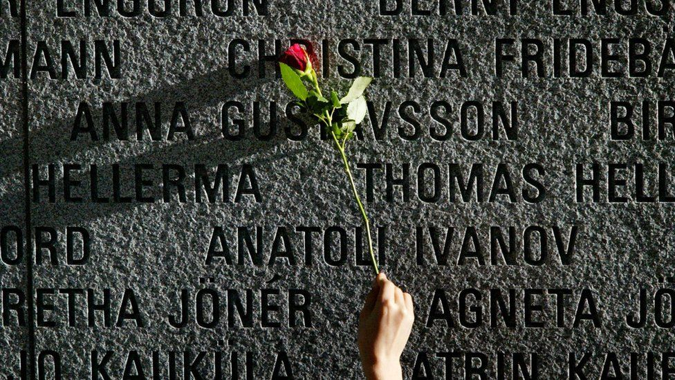 """A flower is pictured on a granite wall bearing the names of the victims of the 1994 sinking of the """"Estonia"""" car ferry in the Baltic Sea in 2004."""