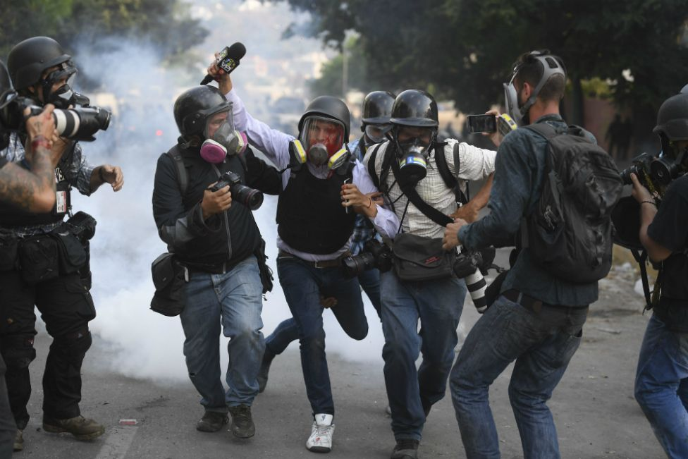 An injured journalist is helped by others during a street protest in Venezuela