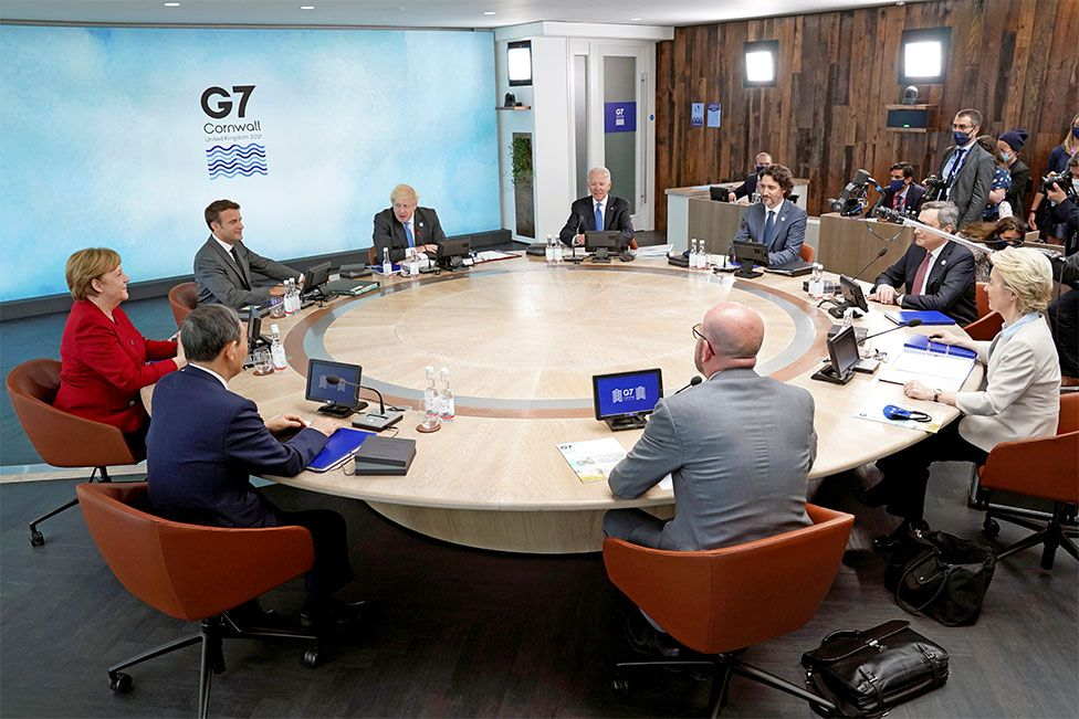 The leaders attending the G7 summit sit around a table in Cornwall