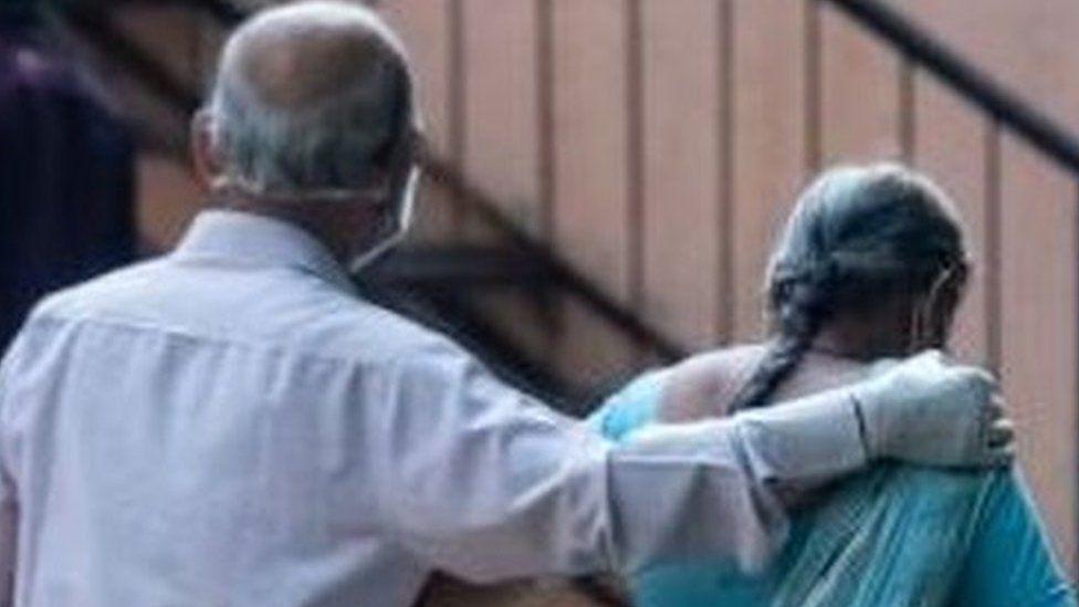 An Indian couple walk towards a hospital