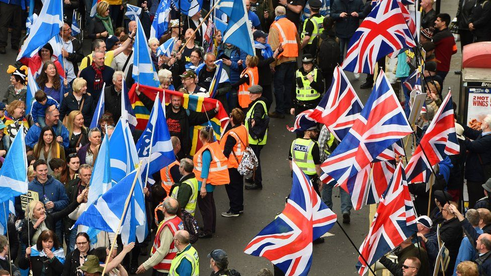 Anti-independence supporters wave Union Jack flags as other demonstrators carry Saltire flags, the national flag of Scotland