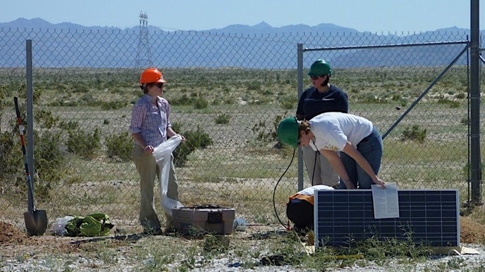 Three scientists handling sensor equipment in front of a chain link fence, desert behind