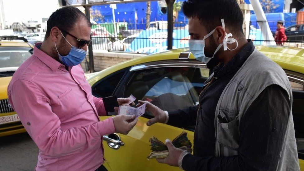 A man pays for petrol at a petrol station in Damascus, Syria (28 March 2020)