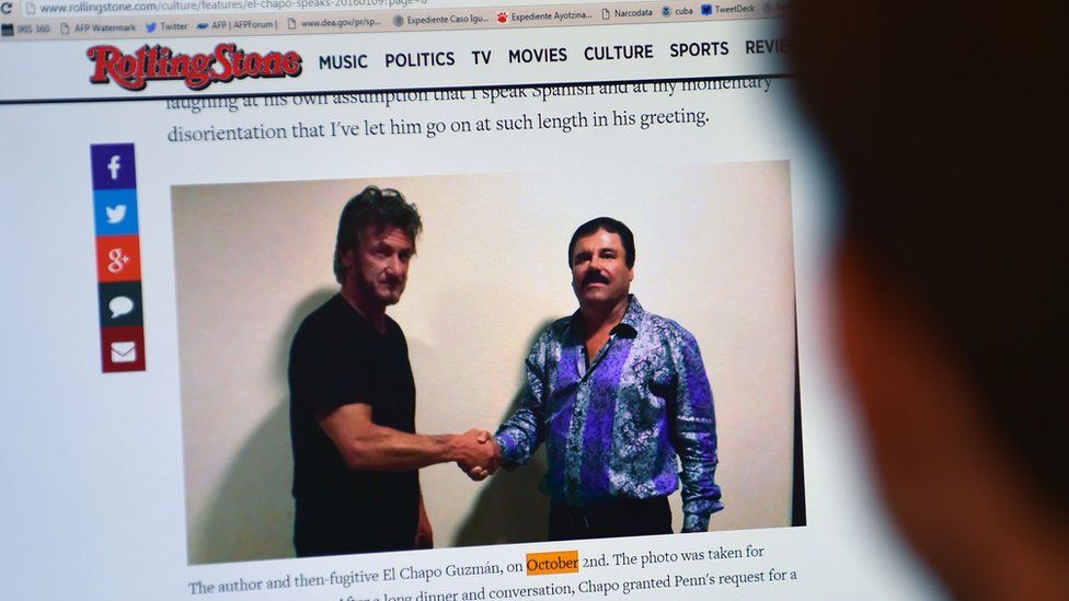 """A man reads an article about drug lord Joaquin Guzman, aka """"El Chapo"""", showing a picture of him (R) and US actor Sean Penn, on the website of Rolling Stone magazine, in Mexico City, on January 10, 2016"""
