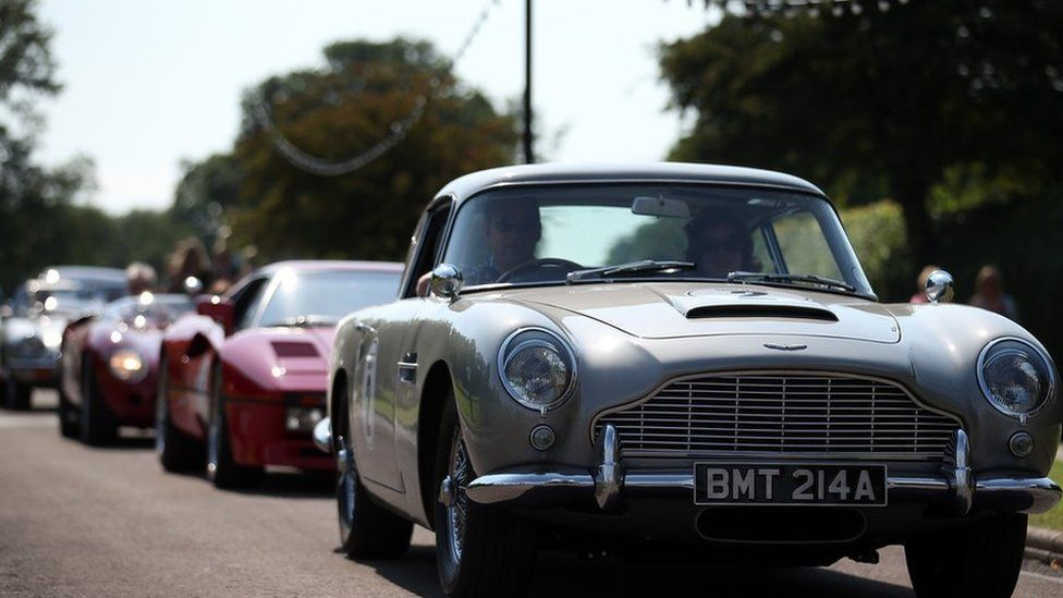 The James Bond Aston Martin DB5 leads a convoy of classic and exotic cars