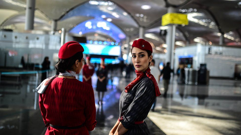 Two Turkish Airlines employees in distinctive red uniforms stand in the shining new halls of the airport, visible stretching behind them. One has her back to the camera, while the other has turned to look directly at the photographer