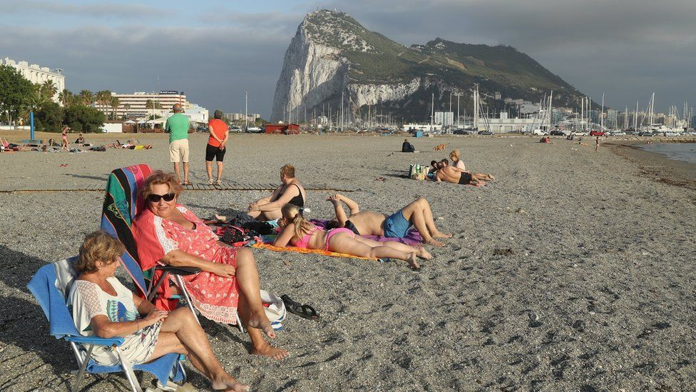 Beachgoers lie in the sand as the British territory of Gibraltar looms behind in La Linea de la Concepcion, Spain (22 June 2016)