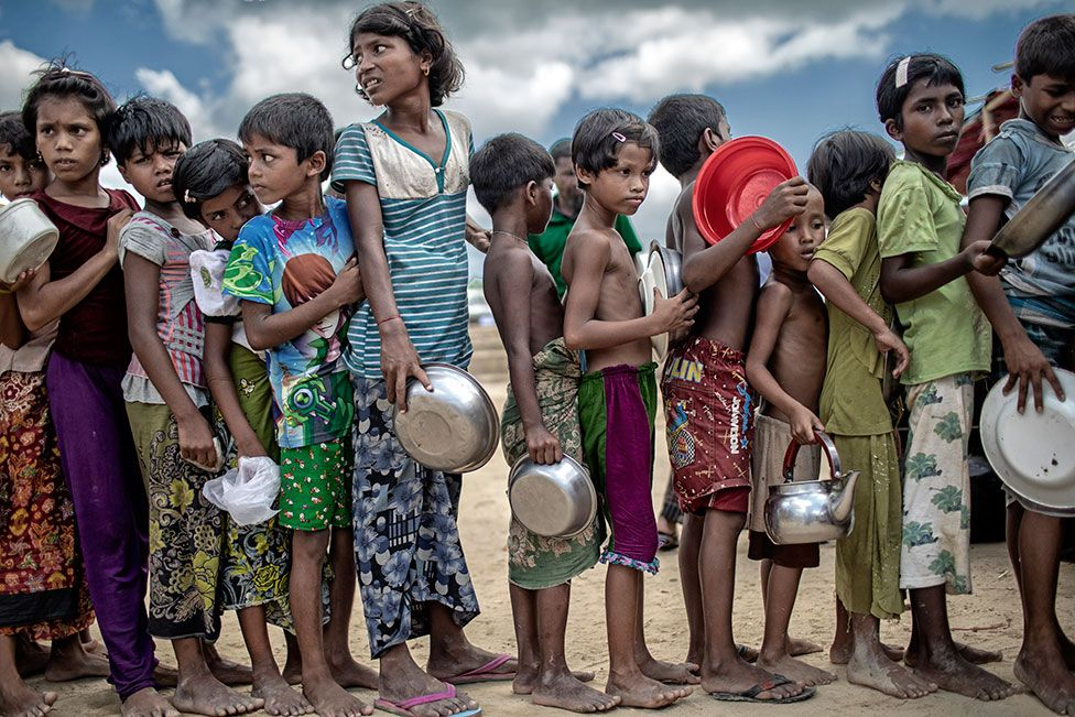 Children holding bowls queuing for food