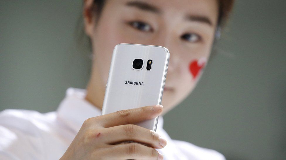A girl holds up her smartphone