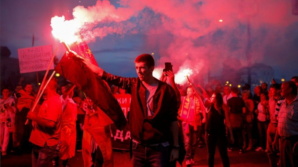 """A supporter of opposition party VMRO-DPMNE lights a flare as he takes part in a protest over compromise solution in Macedonia""""s dispute with Greece over the country""""s name, in Skopje, Macedonia, June 2, 2018."""