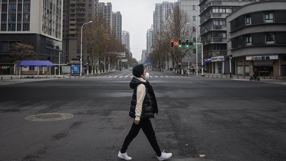 A woman walks on an empty street in Wuhan, China