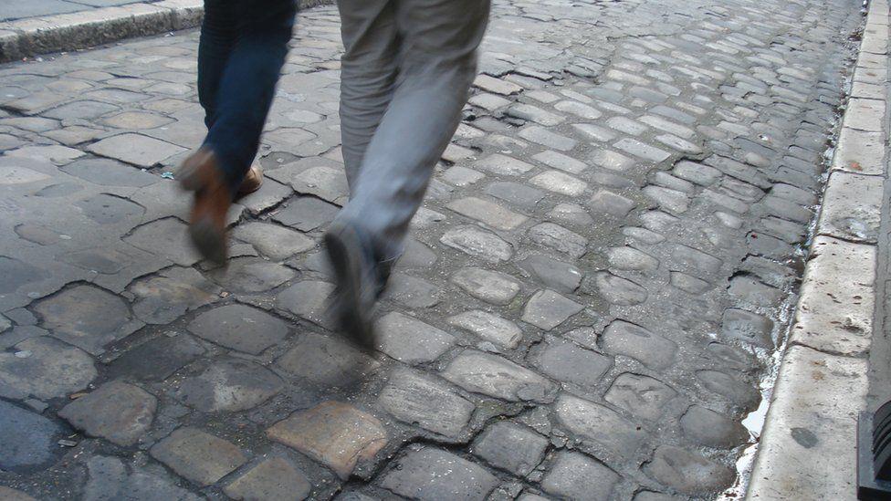 Legs of a couple walking on a cobble street