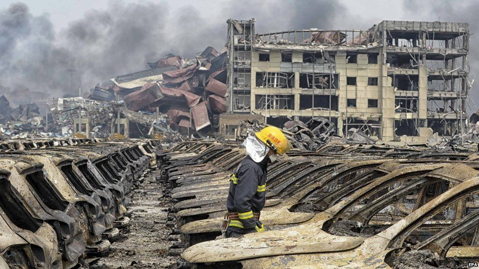 A firefighter walks among damaged vehicles at the site of Wednesday night's explosions in Tianjin, China, on 14 August, 2015