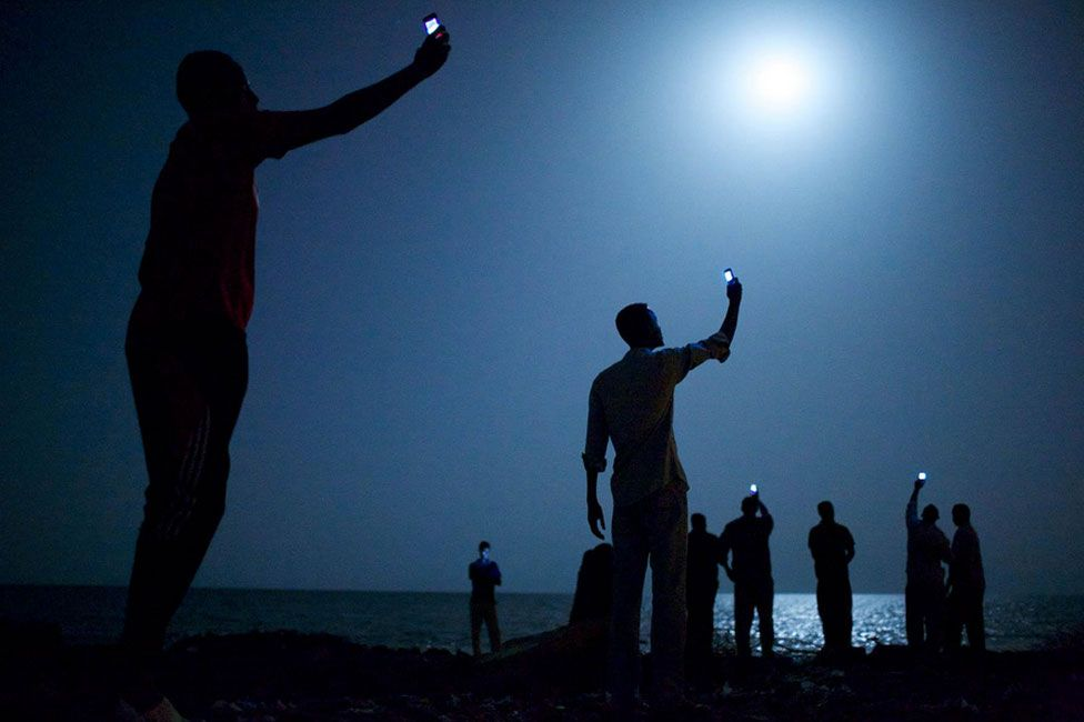Migrants with mobile phones on the beach in Djibouti